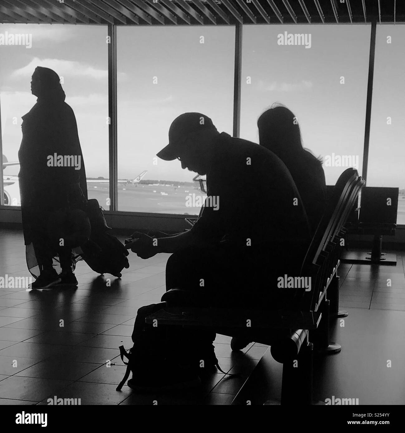 Waiting for a plane brings together all sorts not who ordinarily would never meet. Stock Photo