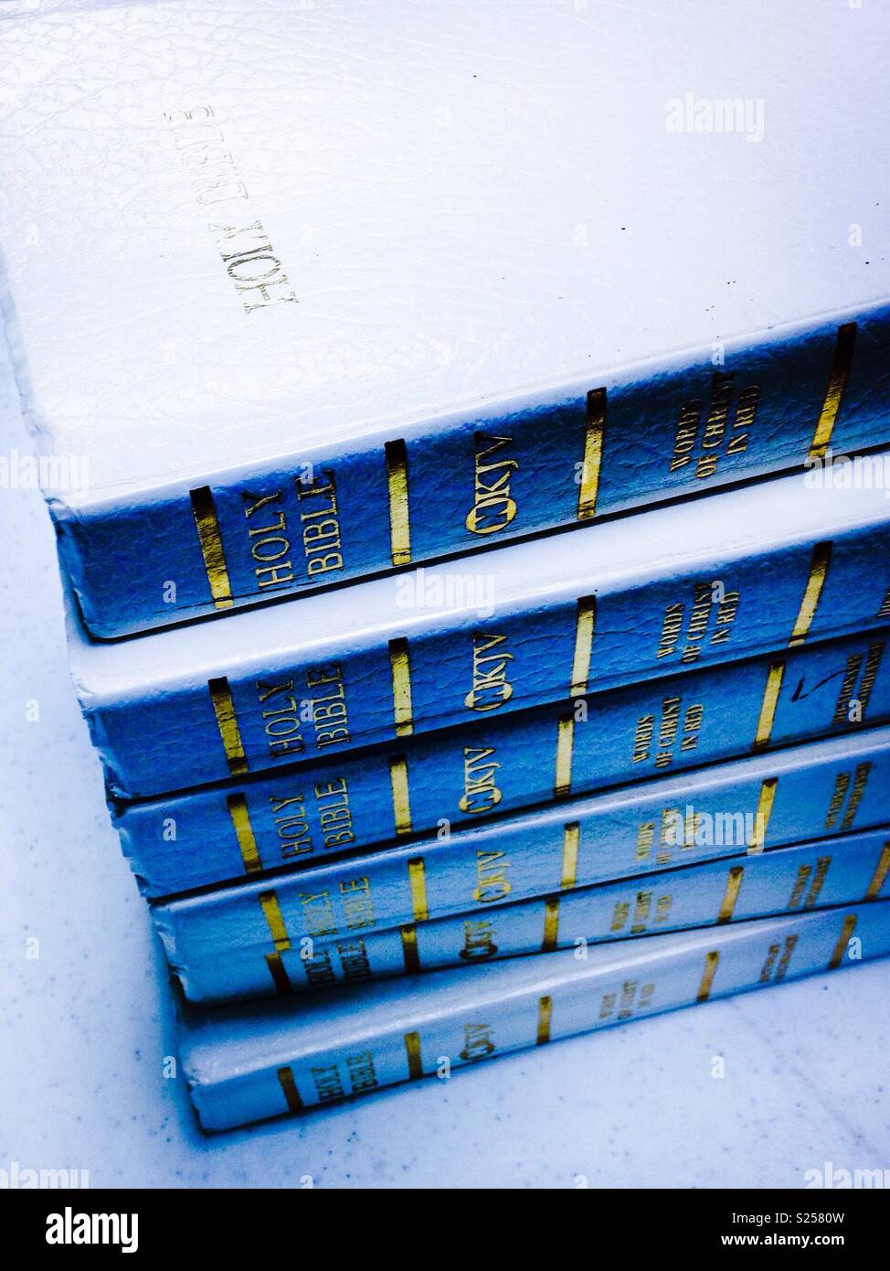 White background, stack of white Sunday School Bibles with blue shadow - Stock Image