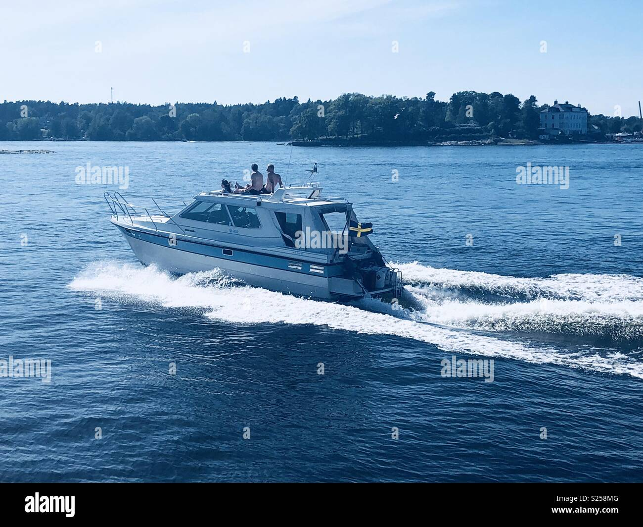 Swedish speed boat in the Stockholm archipelago with people lounging on the top of the boat - Stock Image