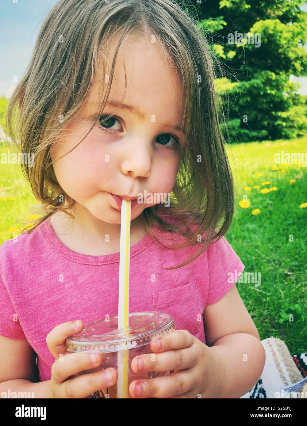 2 Year Old Toddler Girl Drinking Juice From Plastic Cup With Straw
