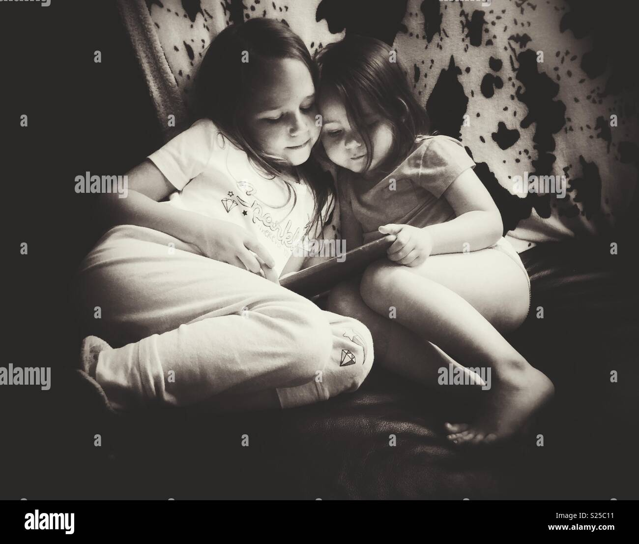 Black and white image of two sisters sitting together looking at a tablet - Stock Image