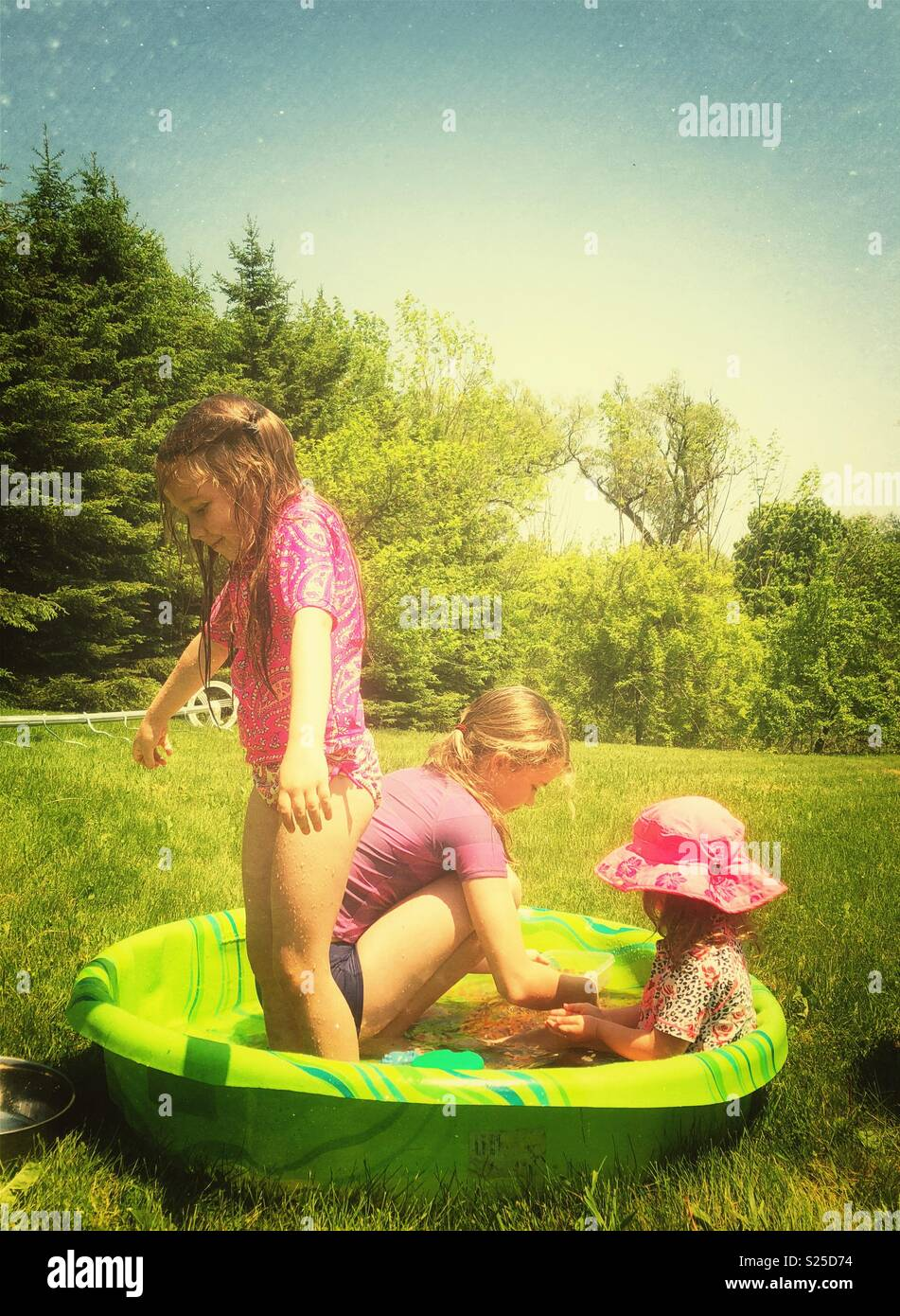 Three sisters playing in a backyard kiddy wading pool on a hot sunny day - Stock Image