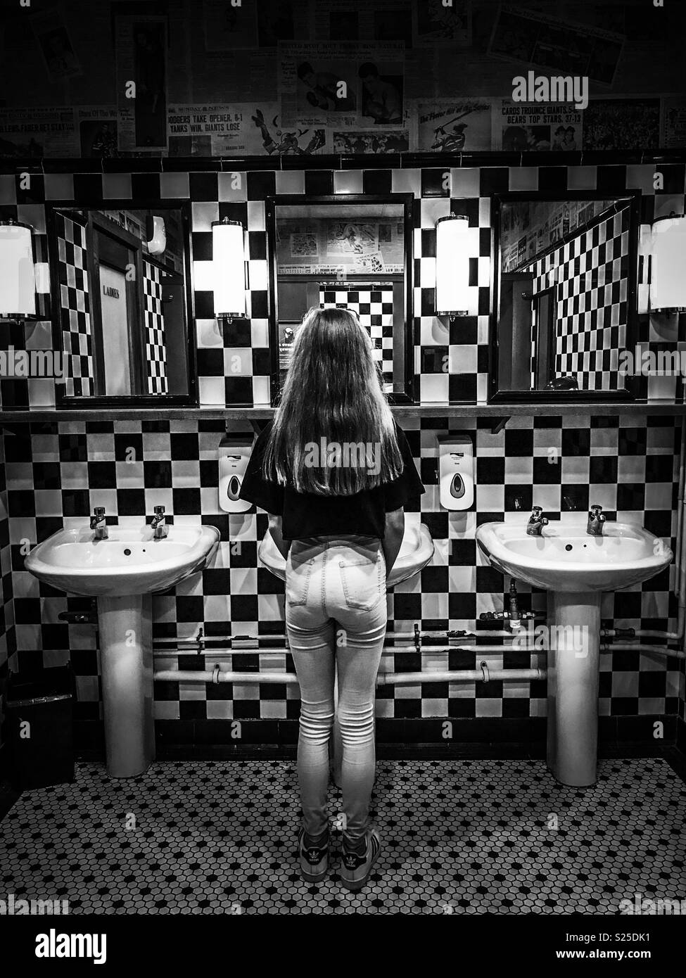 Girl Looking In A Mirror In A Restaurant Bathroom Stock Photo