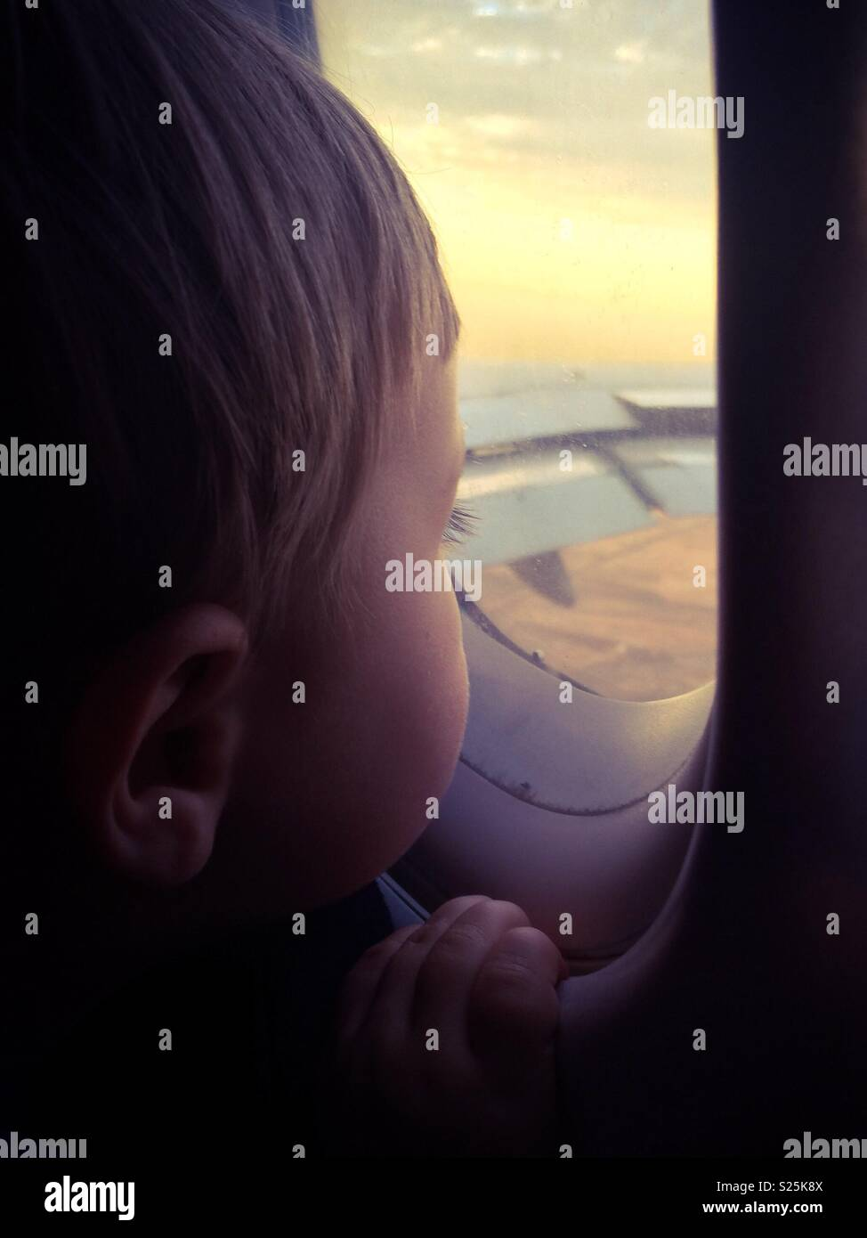 Toddler boy looking out airplane window at sunset while in flight, Autumn filter applied Stock Photo