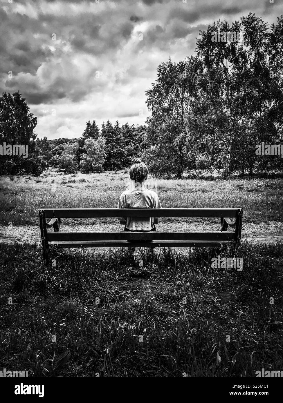 Girl sitting alone on a bench dark skies black and white