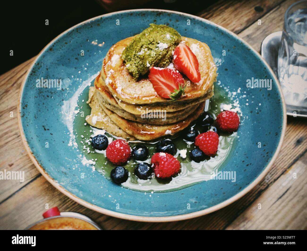 Pancakes with berries on a blue plate on top of a wooden table - Stock Image