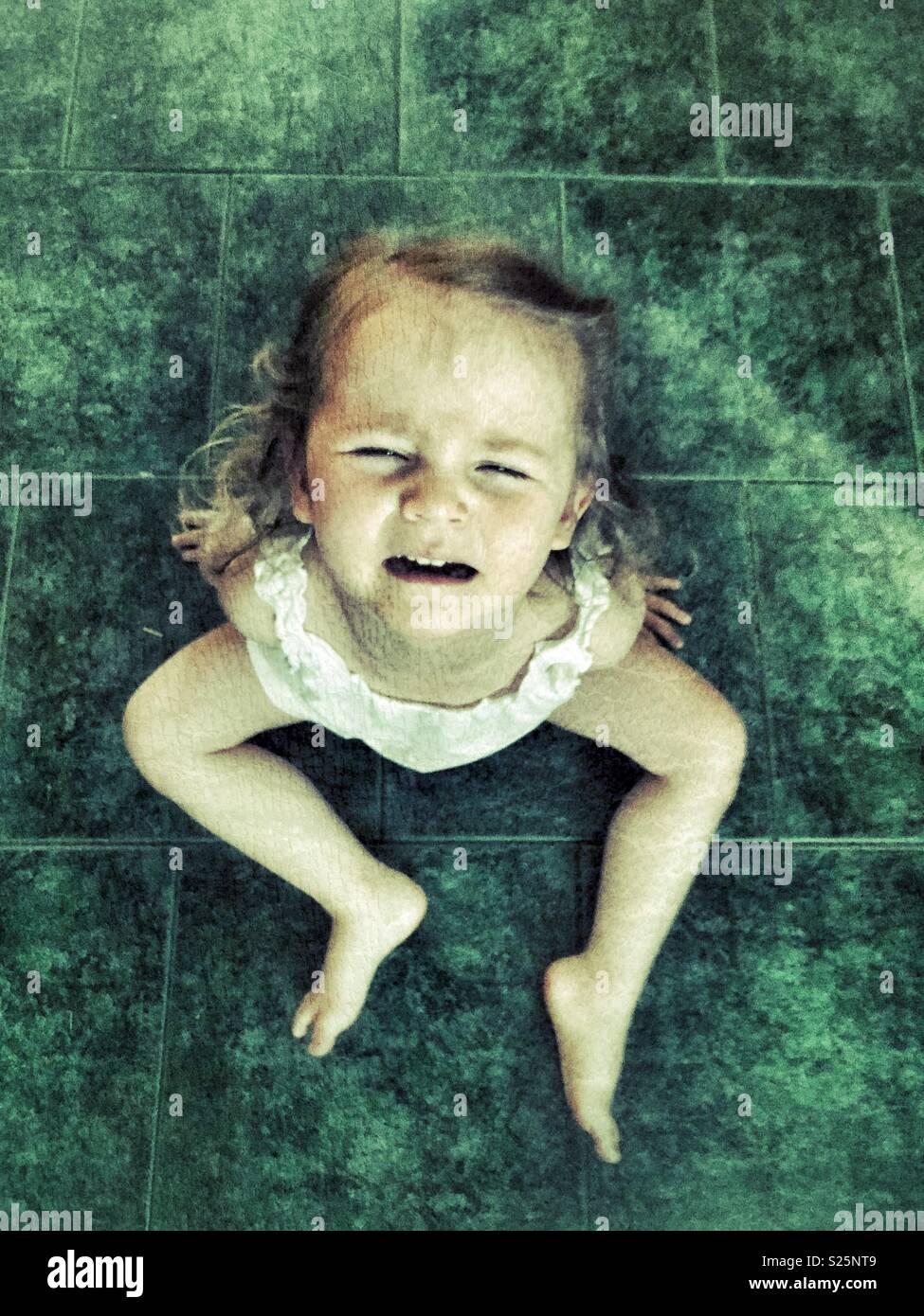 Toddler girl sitting on green tile floor having a temper tantrum - Stock Image