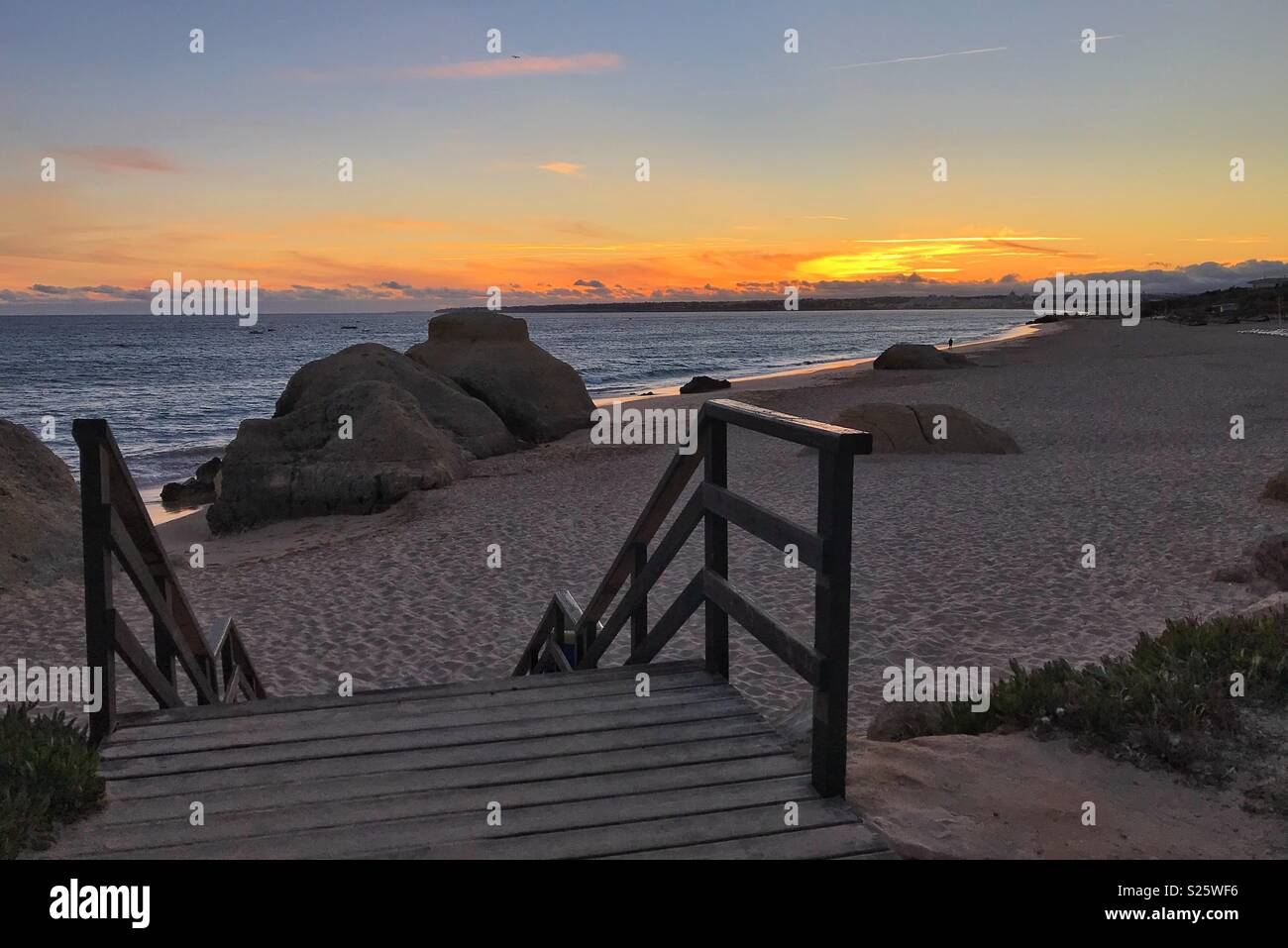 Stairs leading down a picturesque beach at sunset - Stock Image