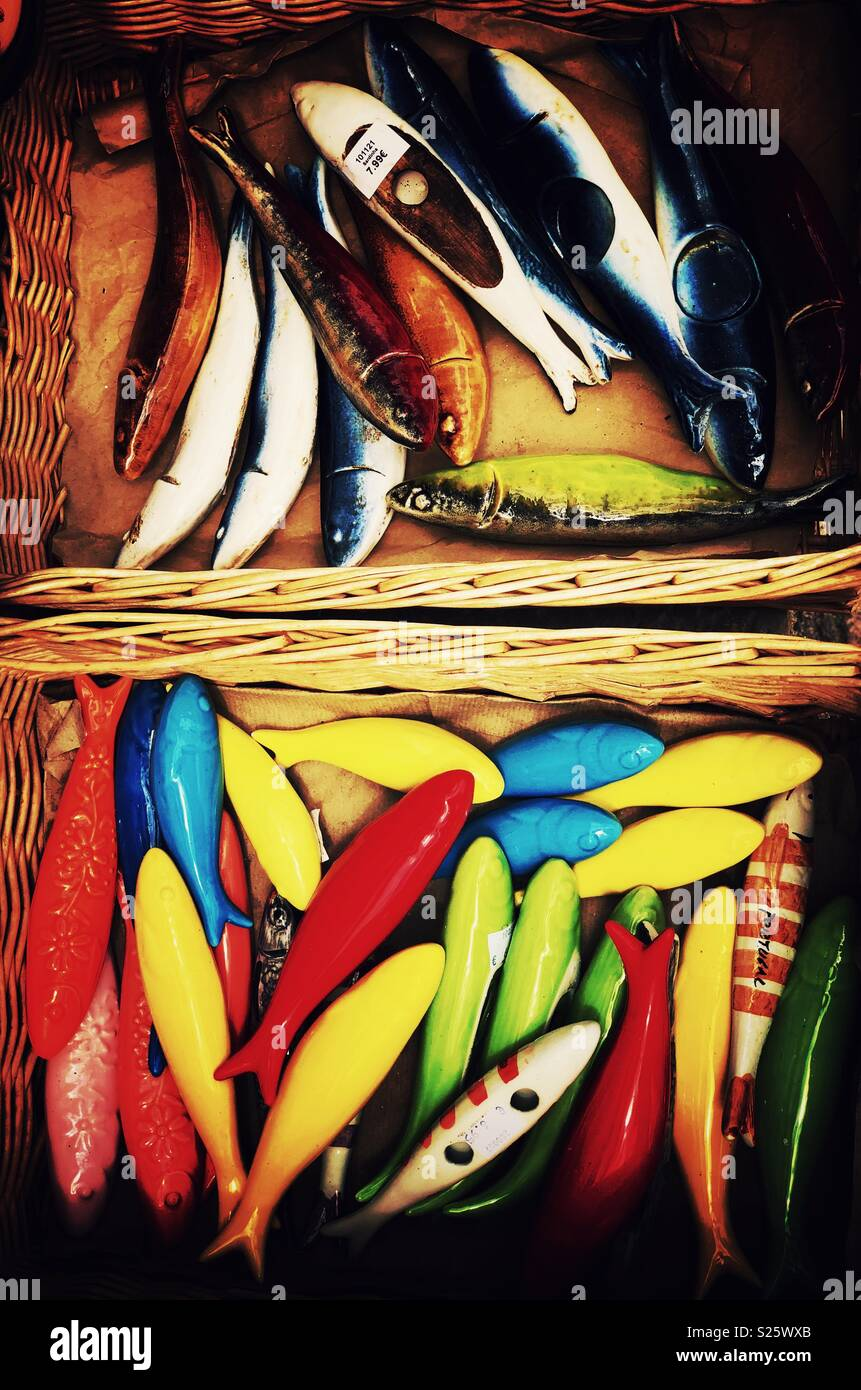 Colourful pieces in the shape of fish for sale in rustic market. Stock Photo