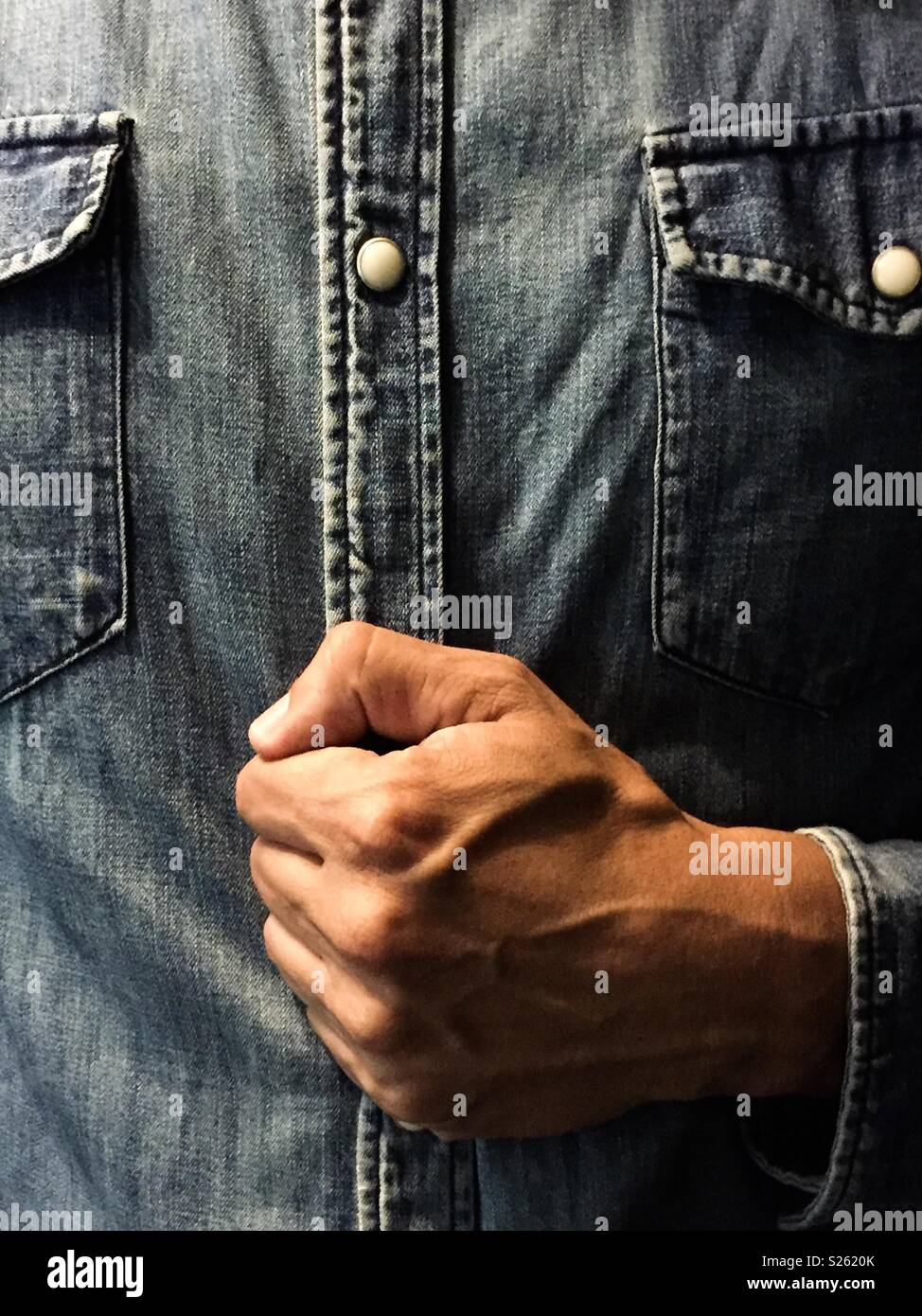 closed fist with a denim shirt - Stock Image