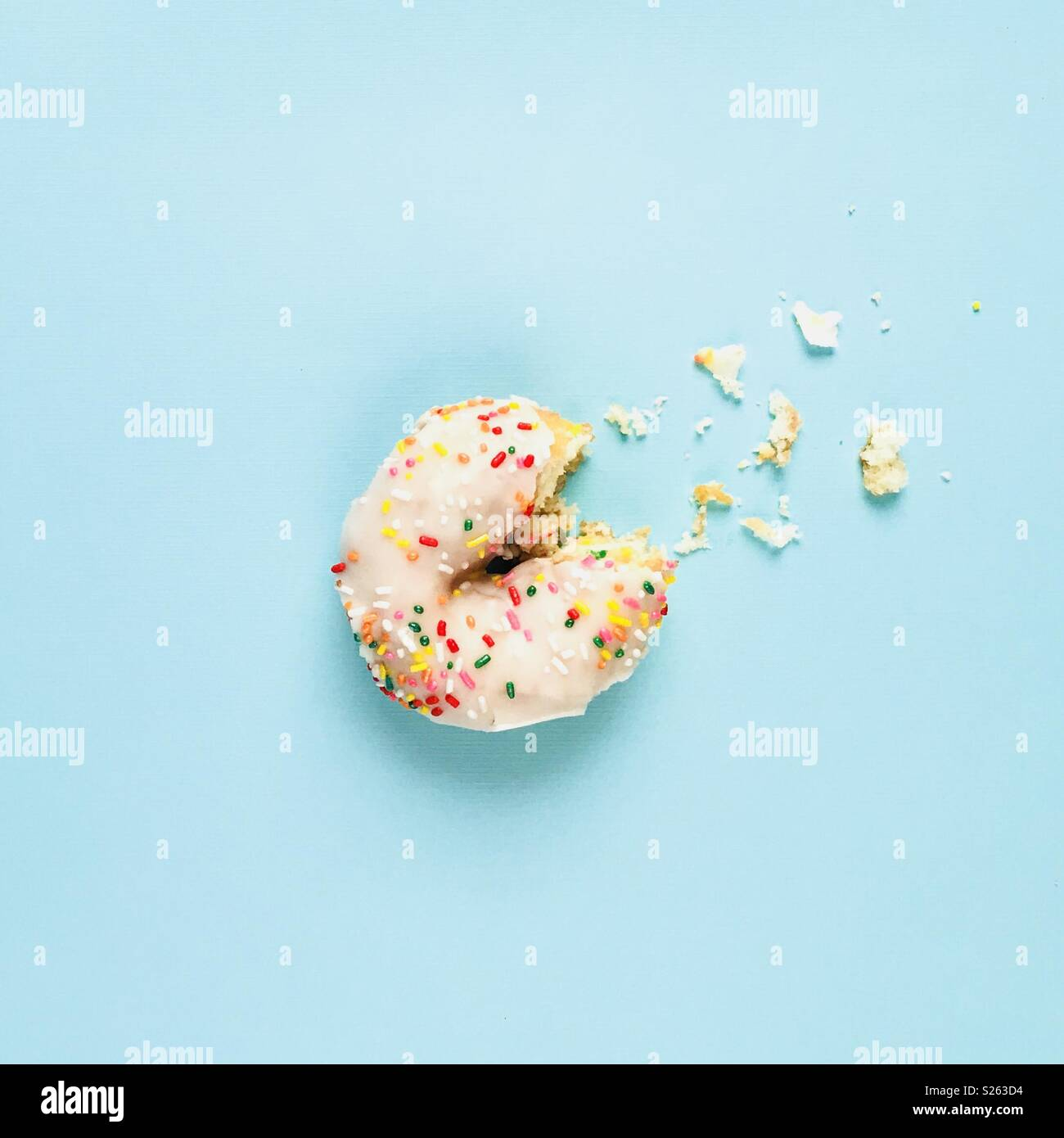 A white sprinkle donut with a bite out of it on a blue background. - Stock Image