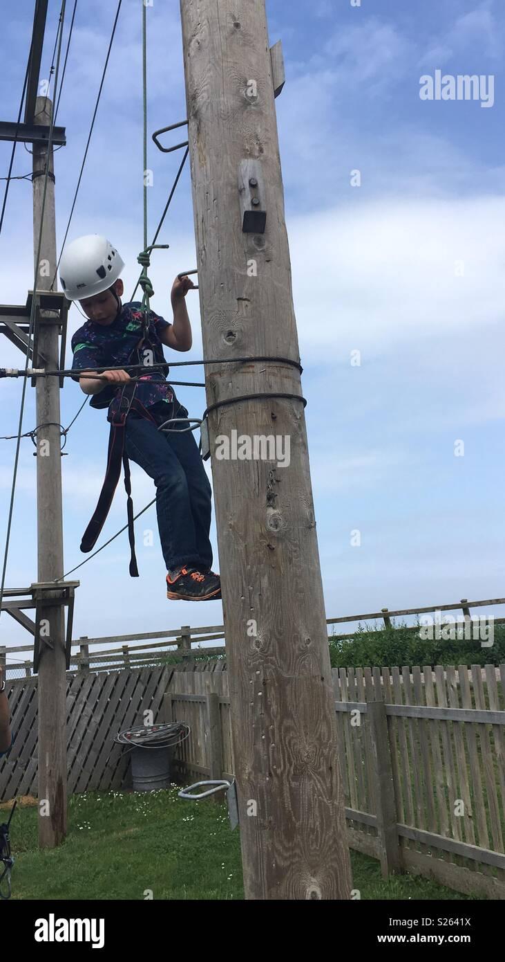 A 7 yr old boy climbing a high wires pole Stock Photo