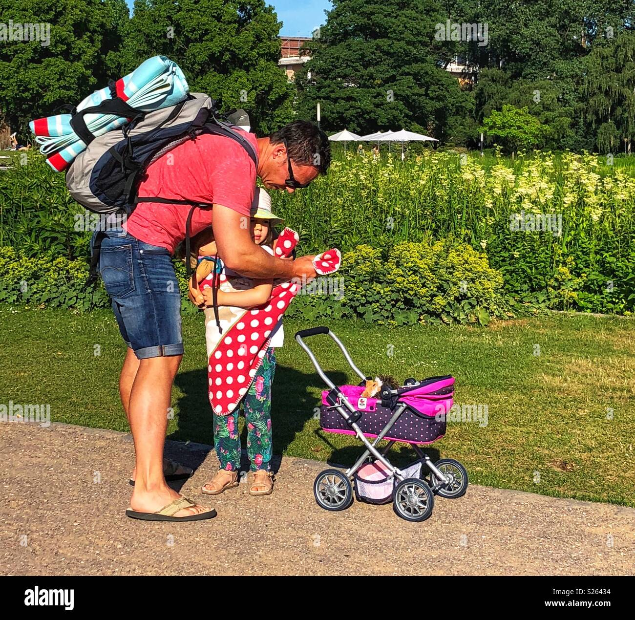 Father helps his daughter with her baby doll. Stock Photo