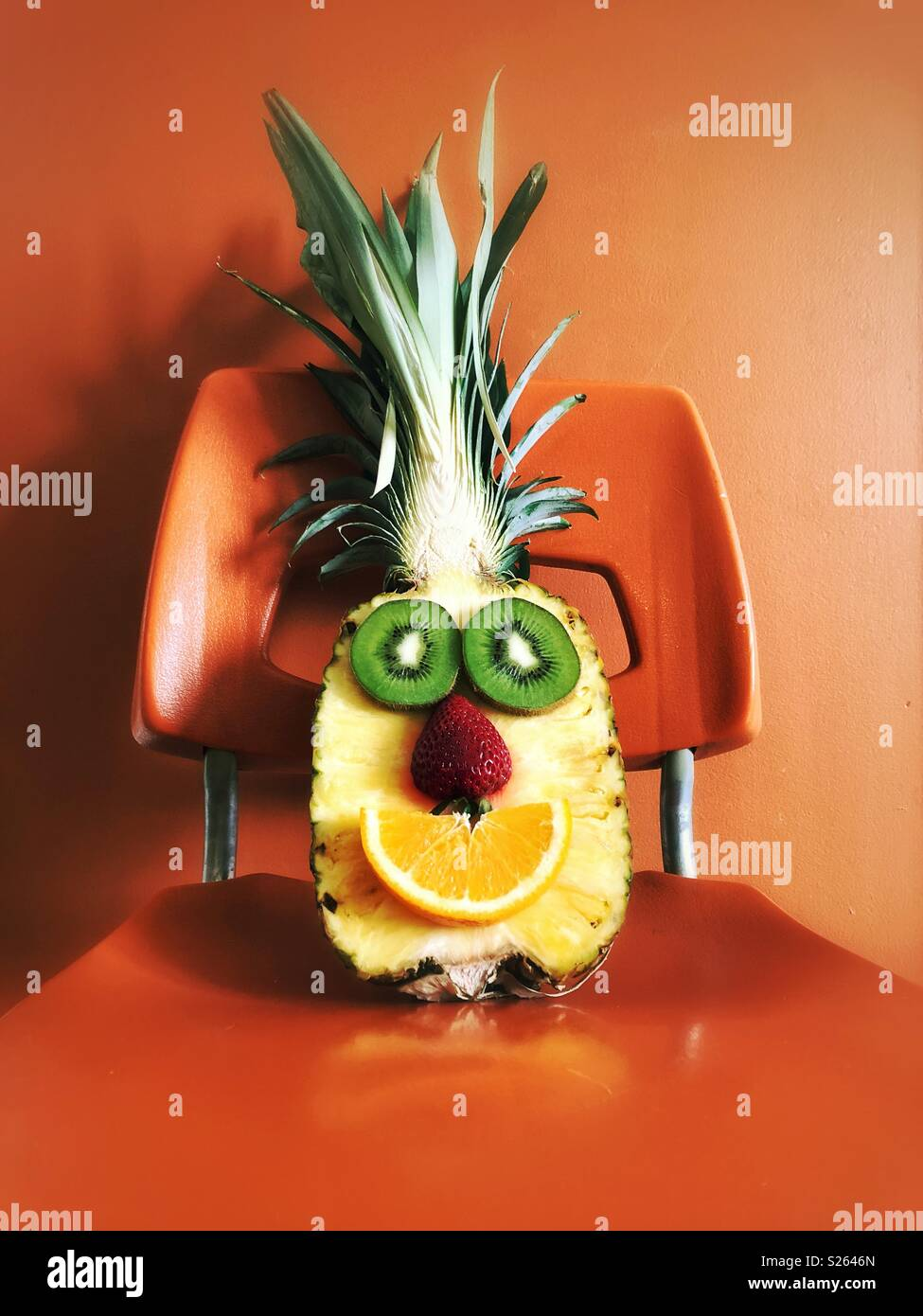 Half pineapple with kiwi slices, strawberry and orange slice made to look like a happy face sitting on an orange chair - Stock Image