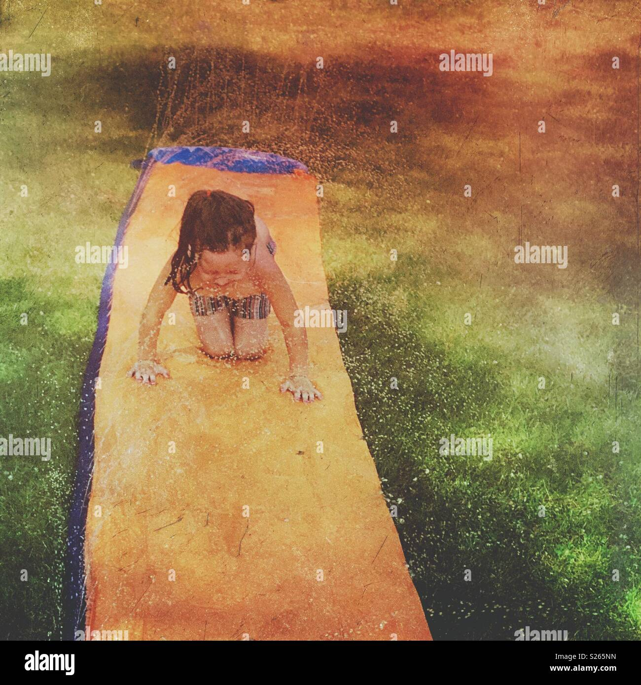 Little girl playing on a slip and slide - Stock Image