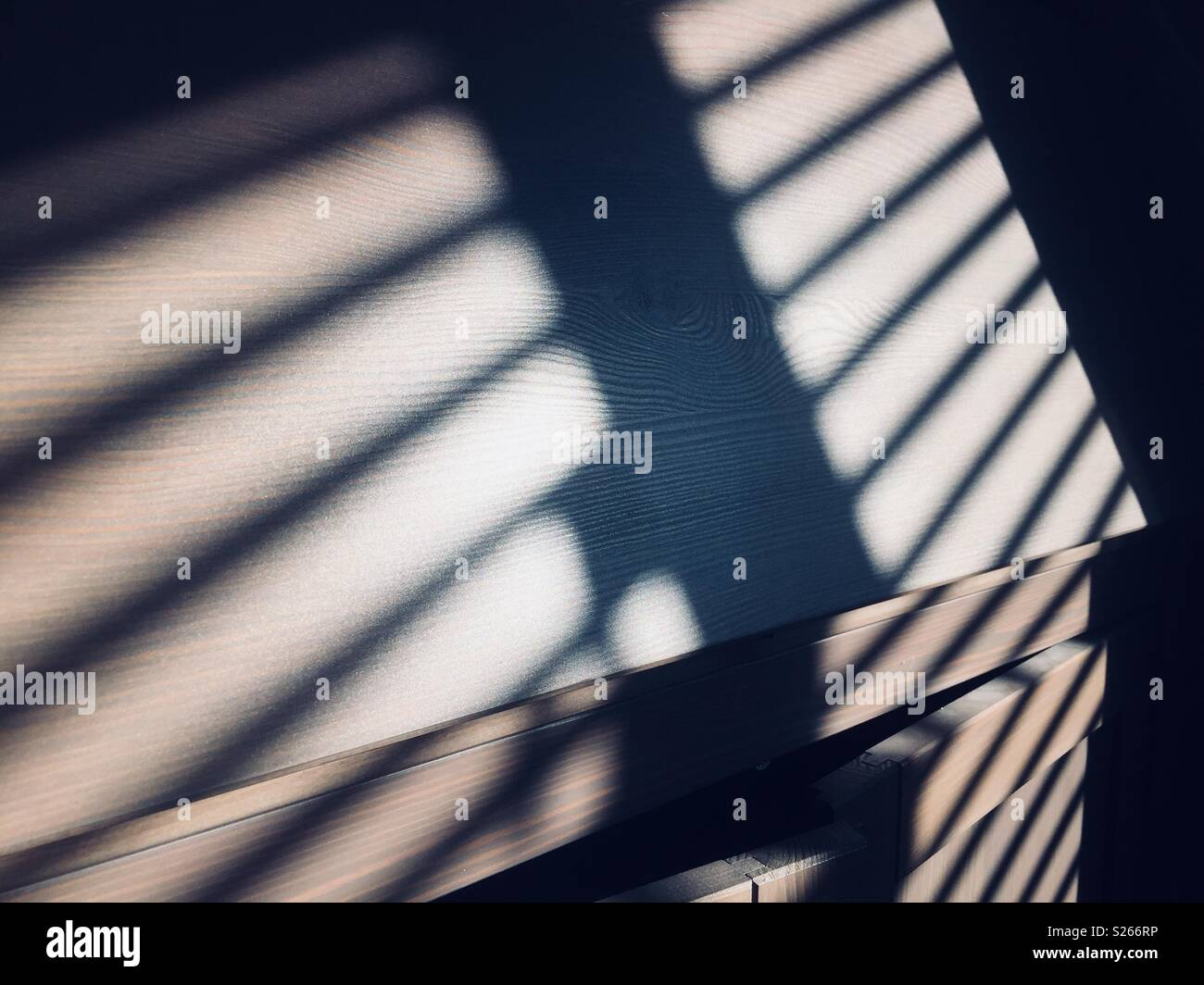 Shadows of a window blind cast on a cabinet by the evening sun - Stock Image