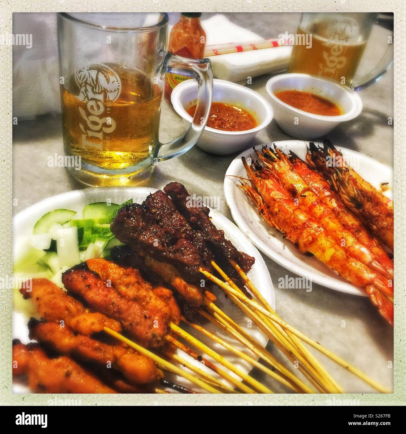 Satay and Tiger beer - dinner at Lau Pa Sat (Telok Ayer Food Market), Singapore - Stock Image