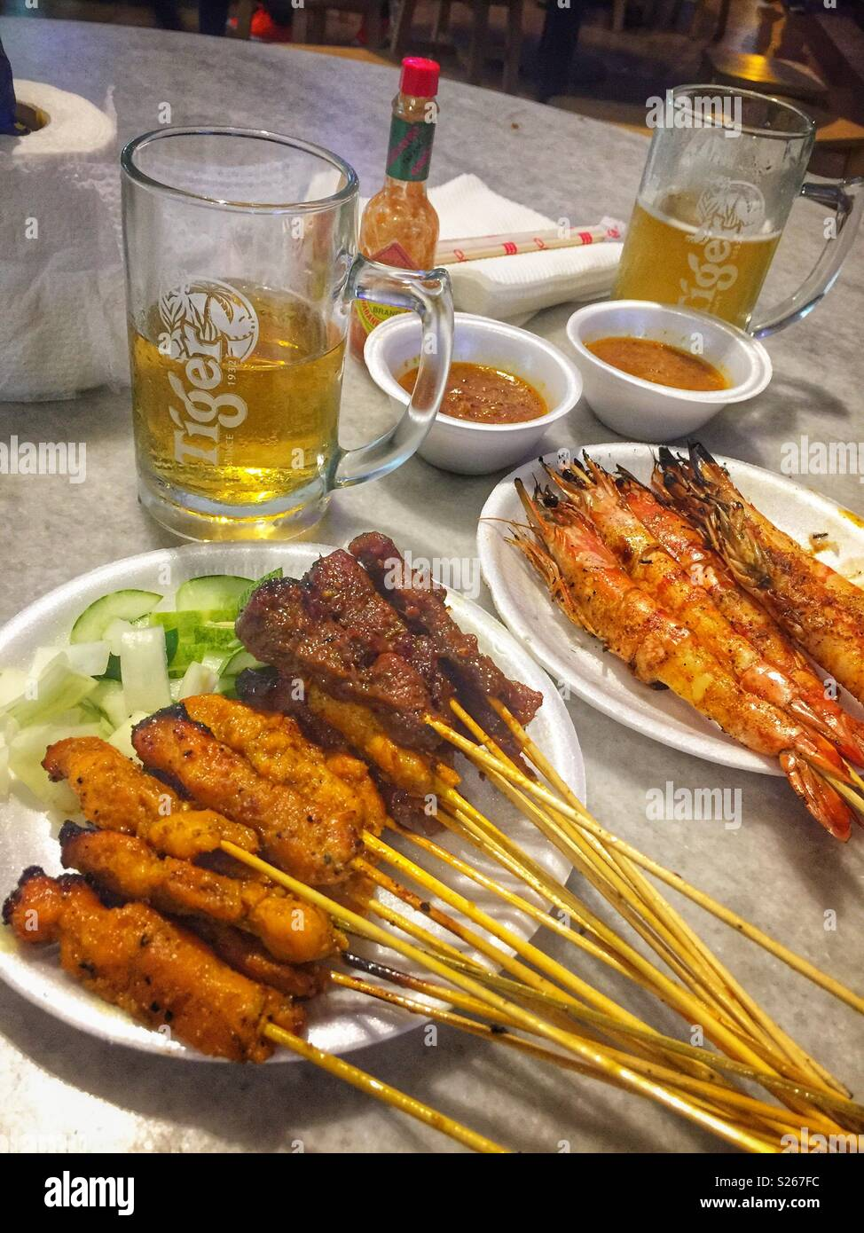 Satay and Tiger beer - dinner at Lau Pa Sat (Telok Ayer Food Market), Singapore - Stock Image
