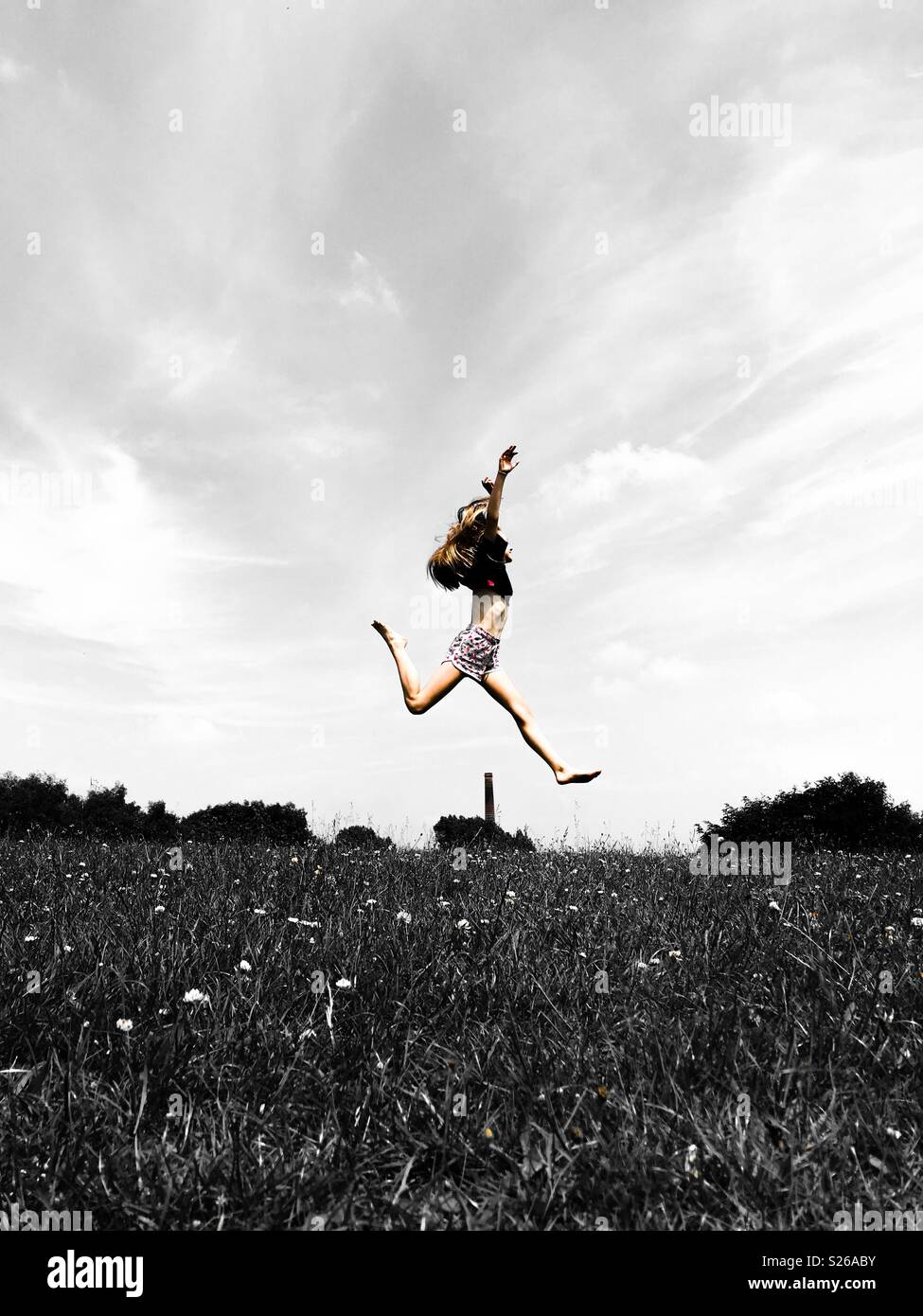 Girl leaping in a field - Stock Image