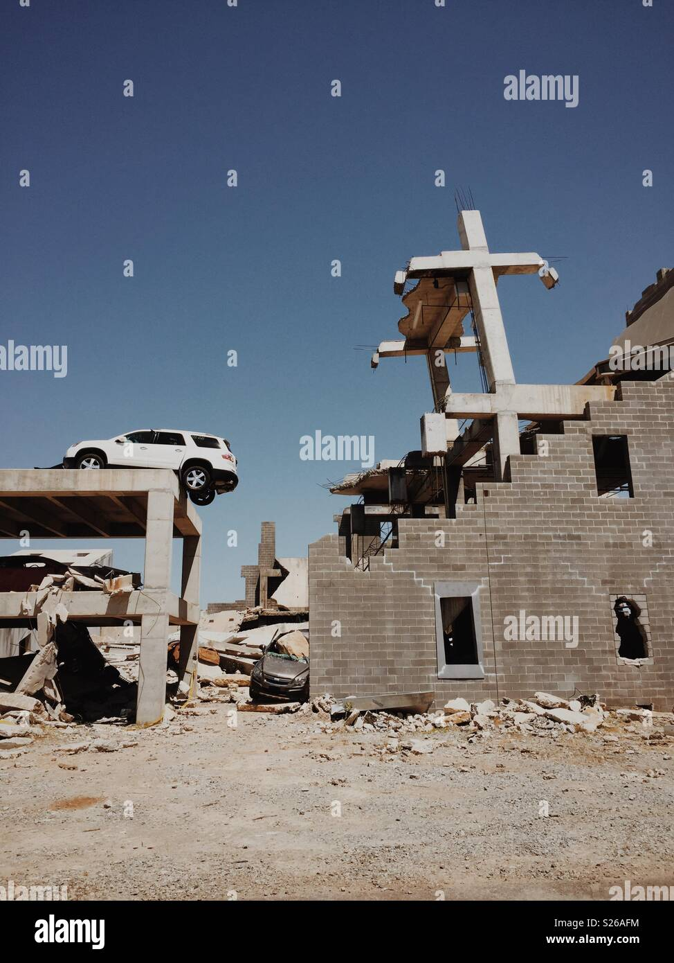 A car teeters on the wreckage of a building. - Stock Image