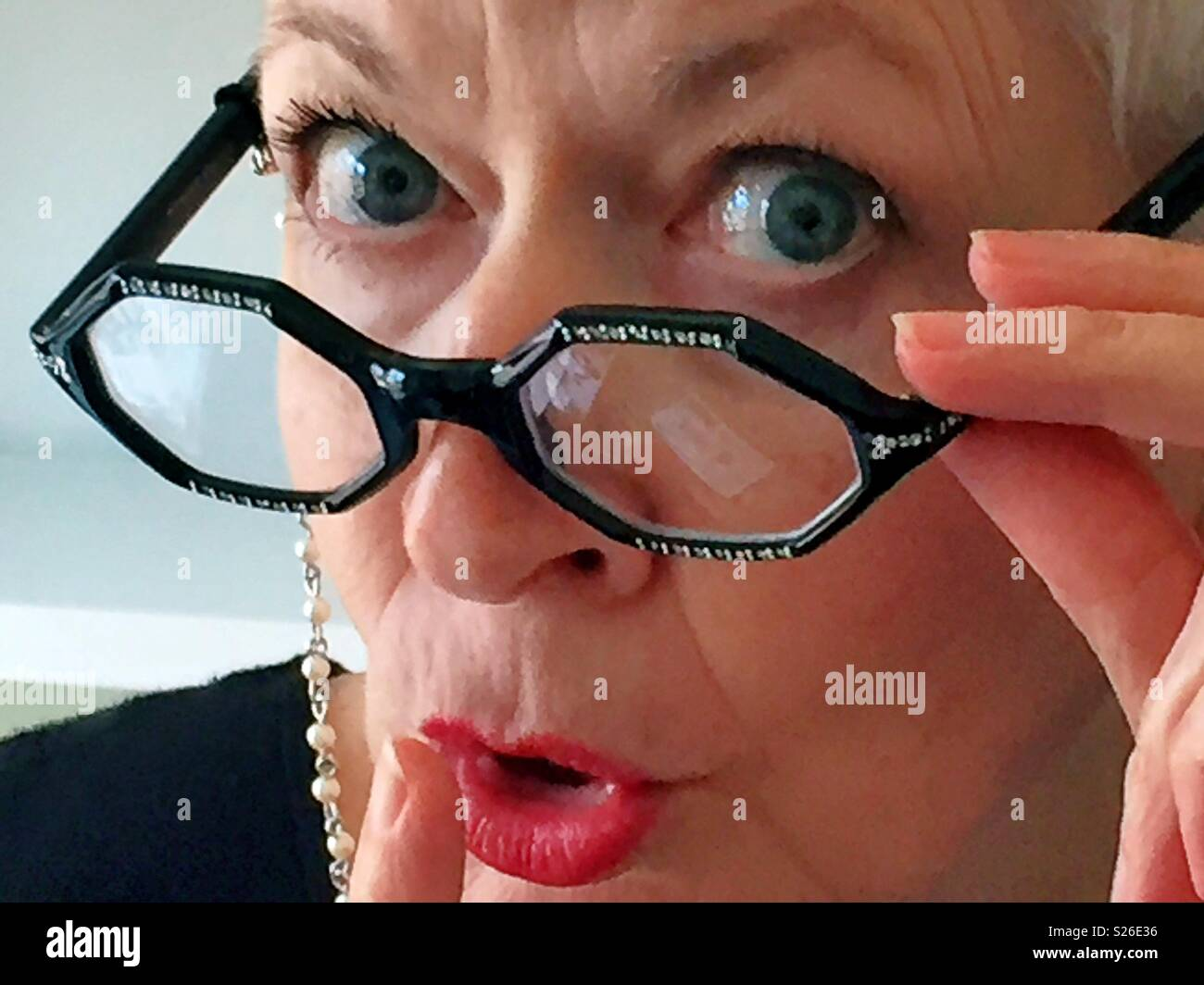 Librarian with vintage eyeglasses and neck chain signaling hush with her finger USA - Stock Image