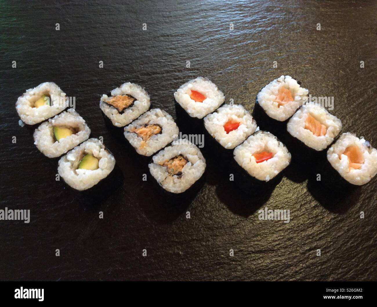 12 mouthwatering Hoso Maki Sushi on Black background in kitchen - Stock Image