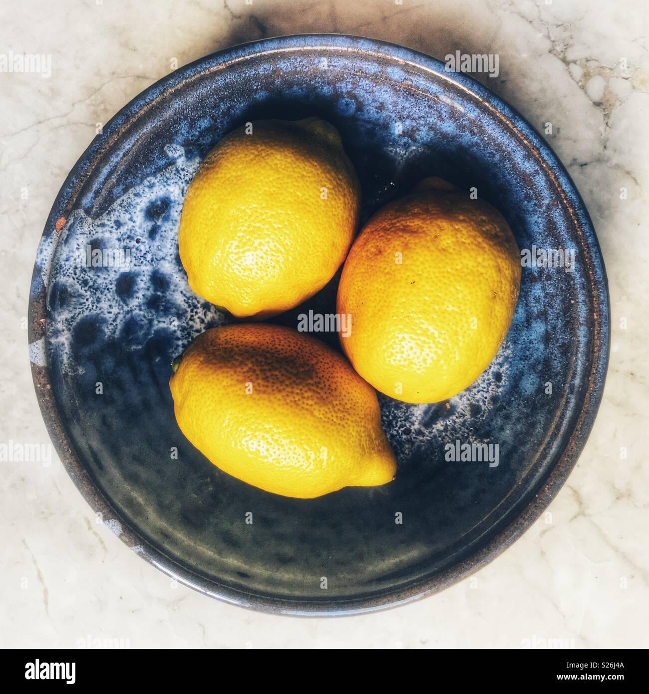 Three fresh lemons in a blue ceramic bowl - Stock Image
