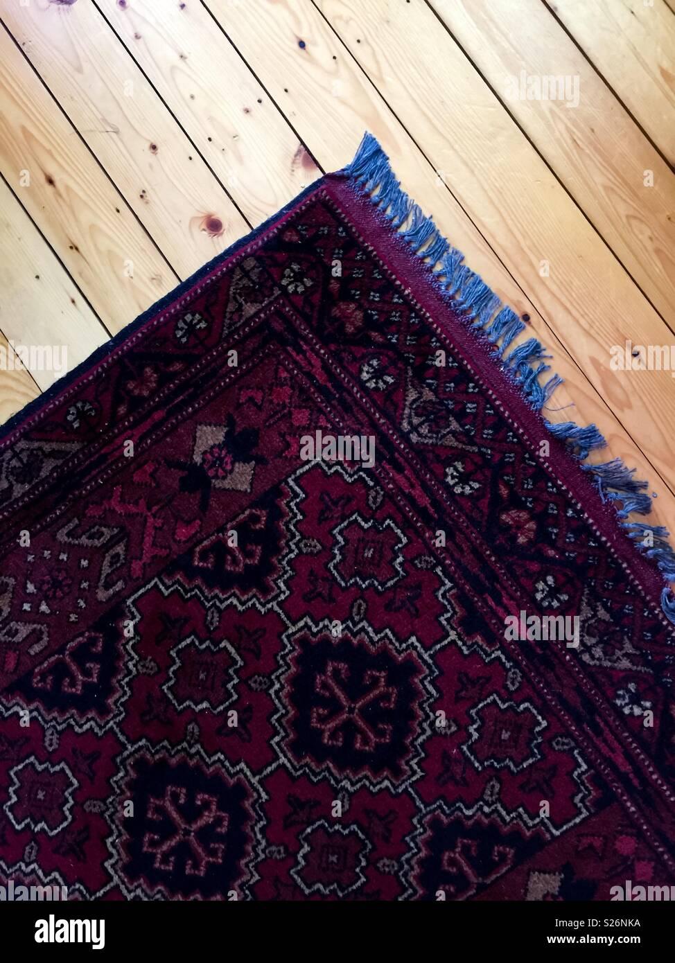 Oriental rug on pine floor - Stock Image
