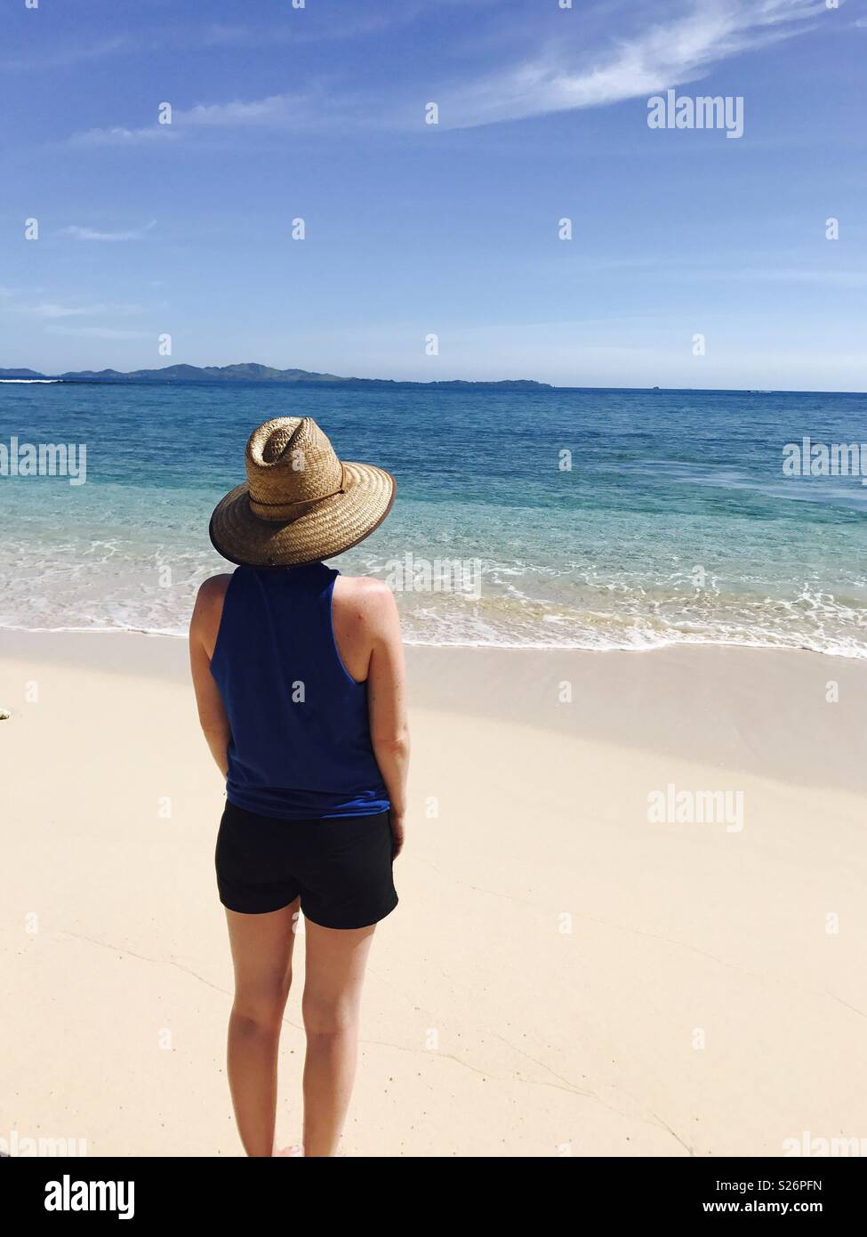 A young women stand in the beach looking at the ocean. Tavarua island resort, Nadi Fiji. - Stock Image