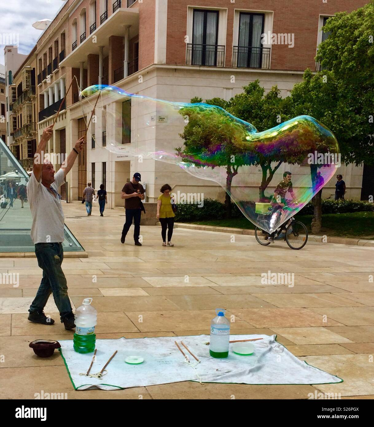 Blowing bubbles; man making huge bubble in Malaga - Stock Image