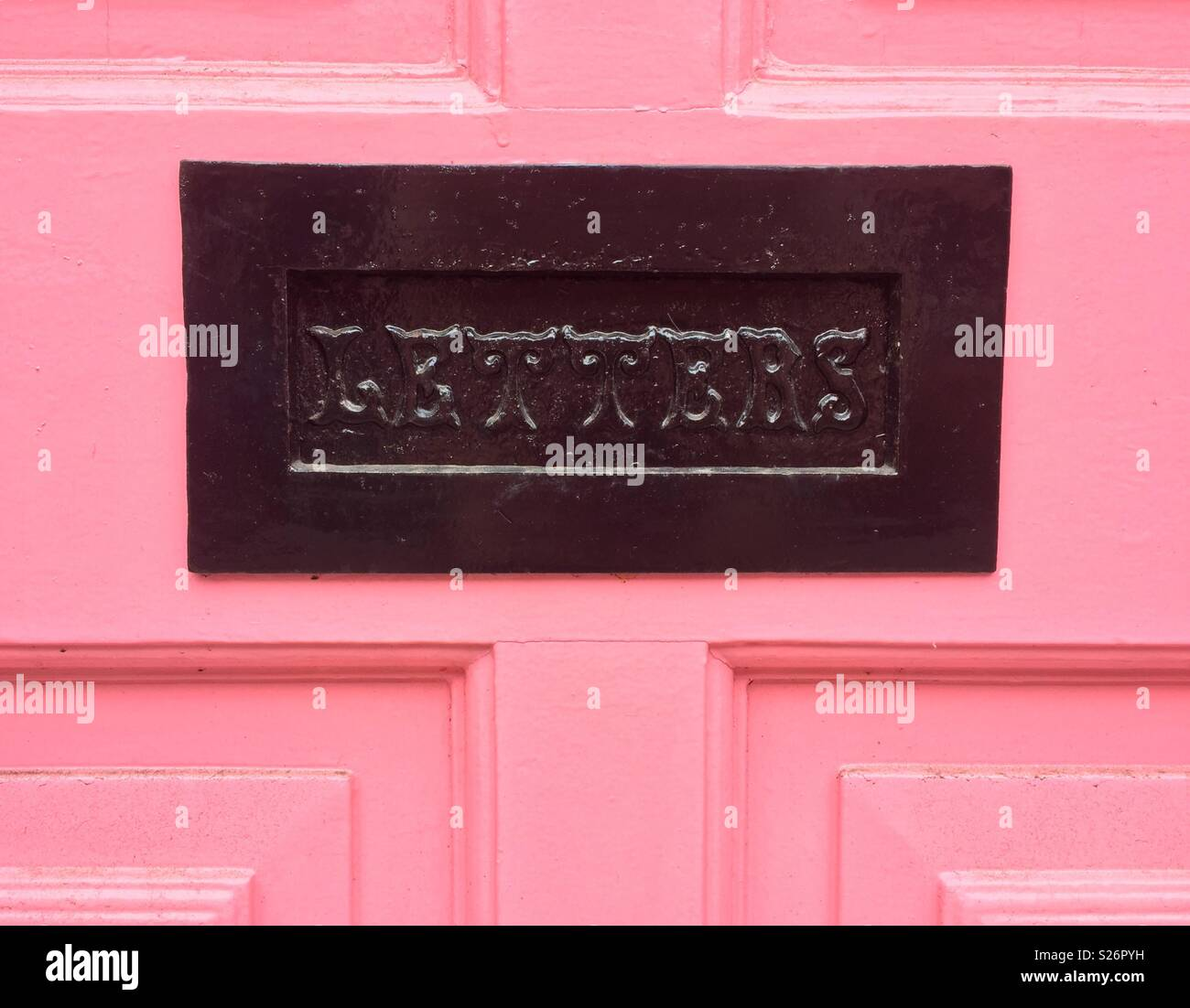 Black letterbox with letters written on, on a pink door. - Stock Image