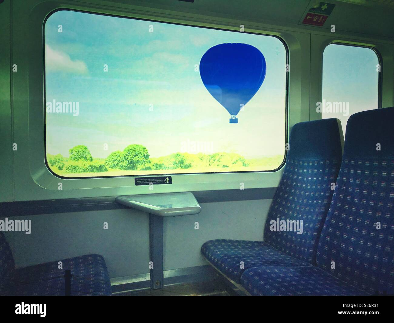 A hot air balloon outside the window of a train - Stock Image