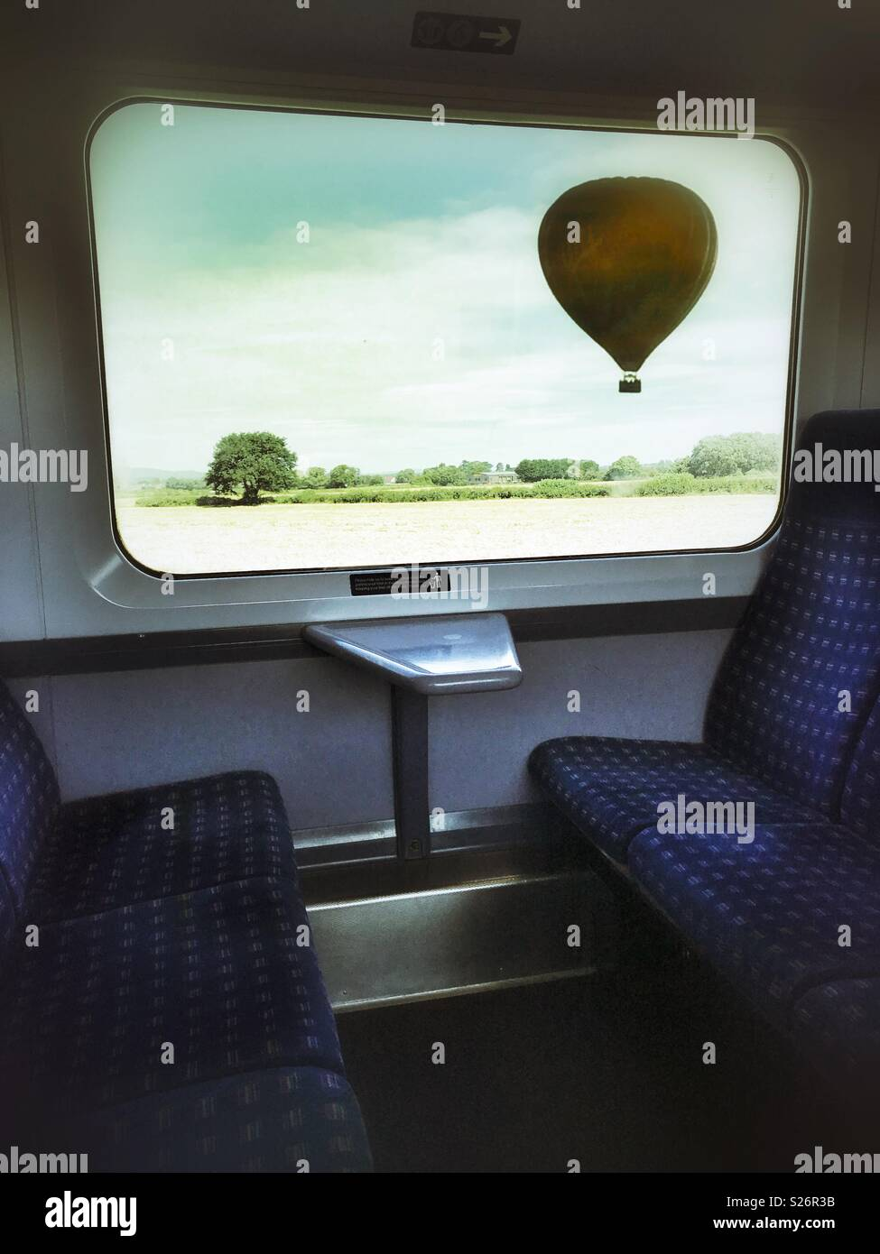 A hot air balloon from the window of an empty train. - Stock Image