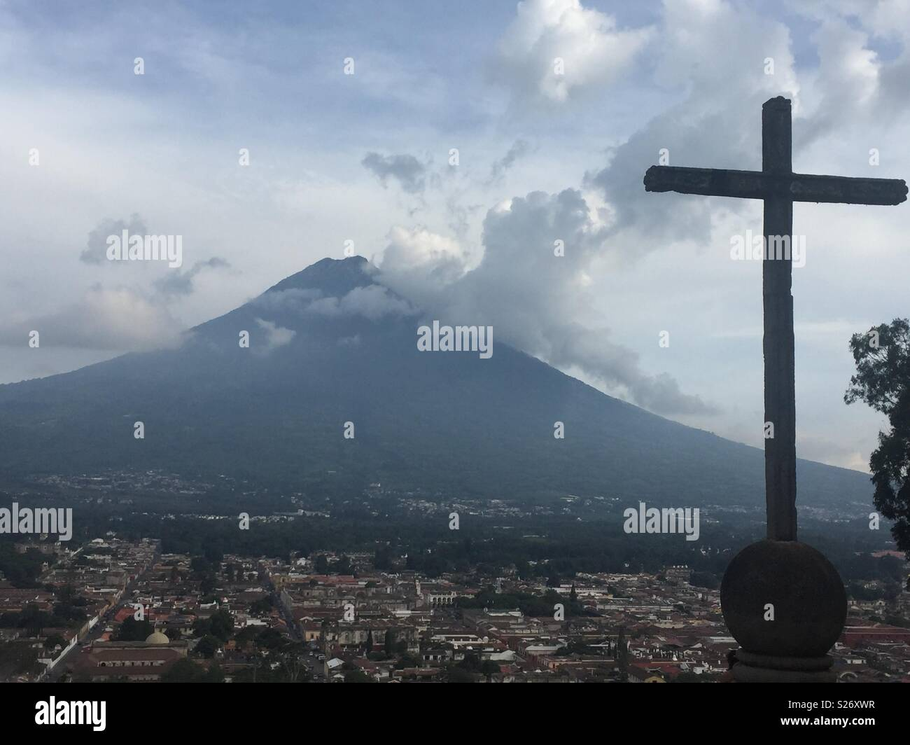 Sitting at Cerro de la Cruz view point, watching the clouds and ash clouds drift across the Volcan Agua, from the recent Volcan Fuego eruption. - Stock Image