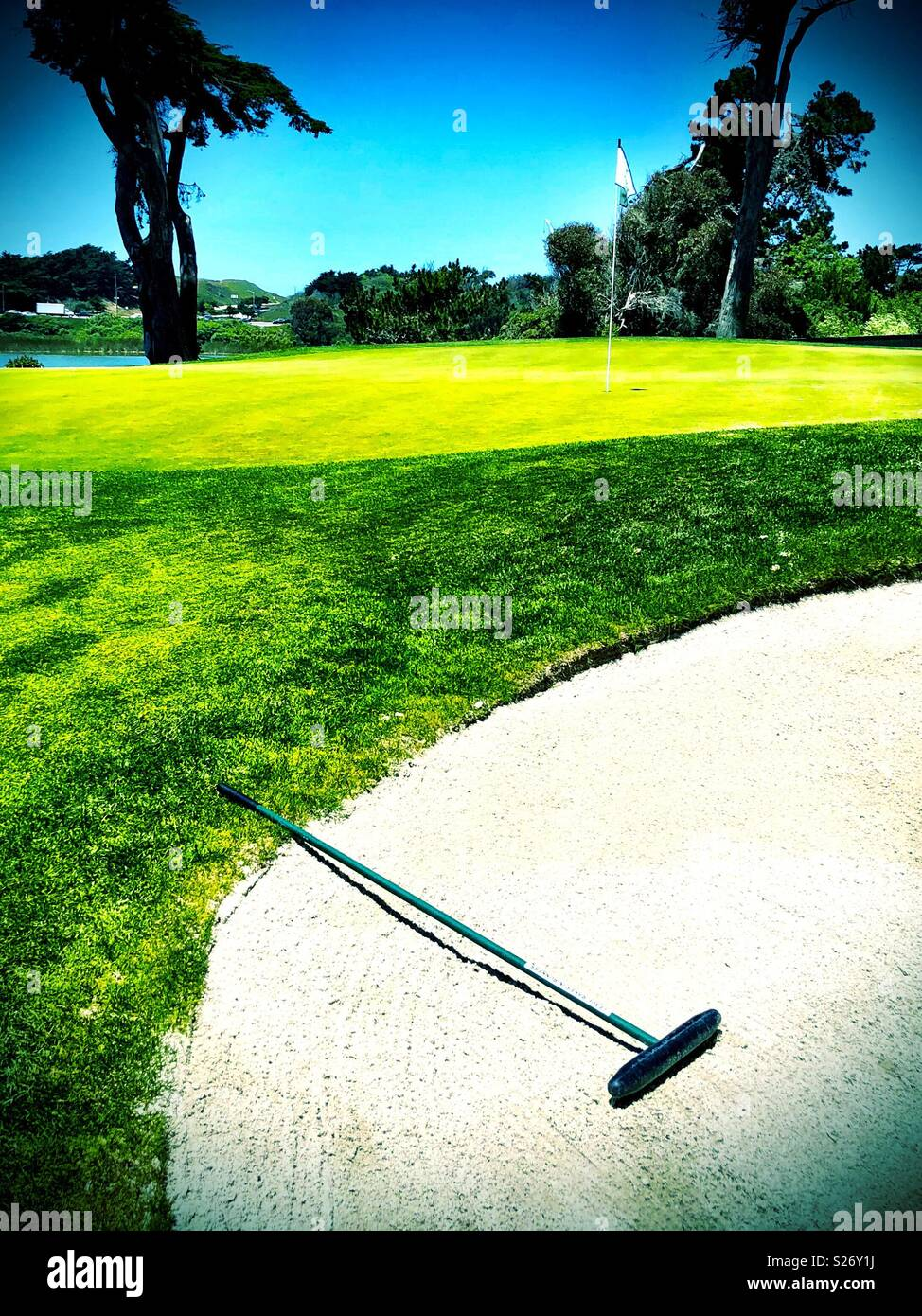 Bunker rake in sand trap with golfing green and lake in the background. - Stock Image