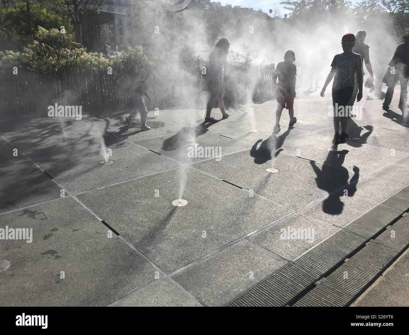 Paris. France. People walking among cooling mist on a hot summer day - Stock Image