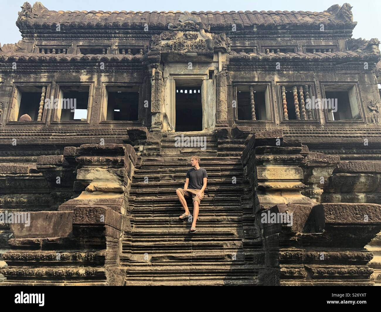 Temples of Angkor Wat ruins in Cambodia with man on steps - Stock Image