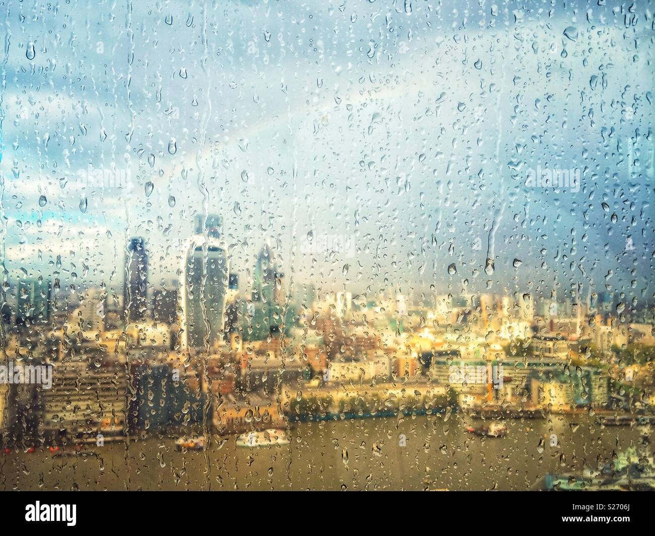 Rain on the window of The Shard, London, UK, looking across the Thames towards Fenchurch Street and over the City. A rainbow lights up the sky as the sun breaks through, lighting up the city below. - Stock Image
