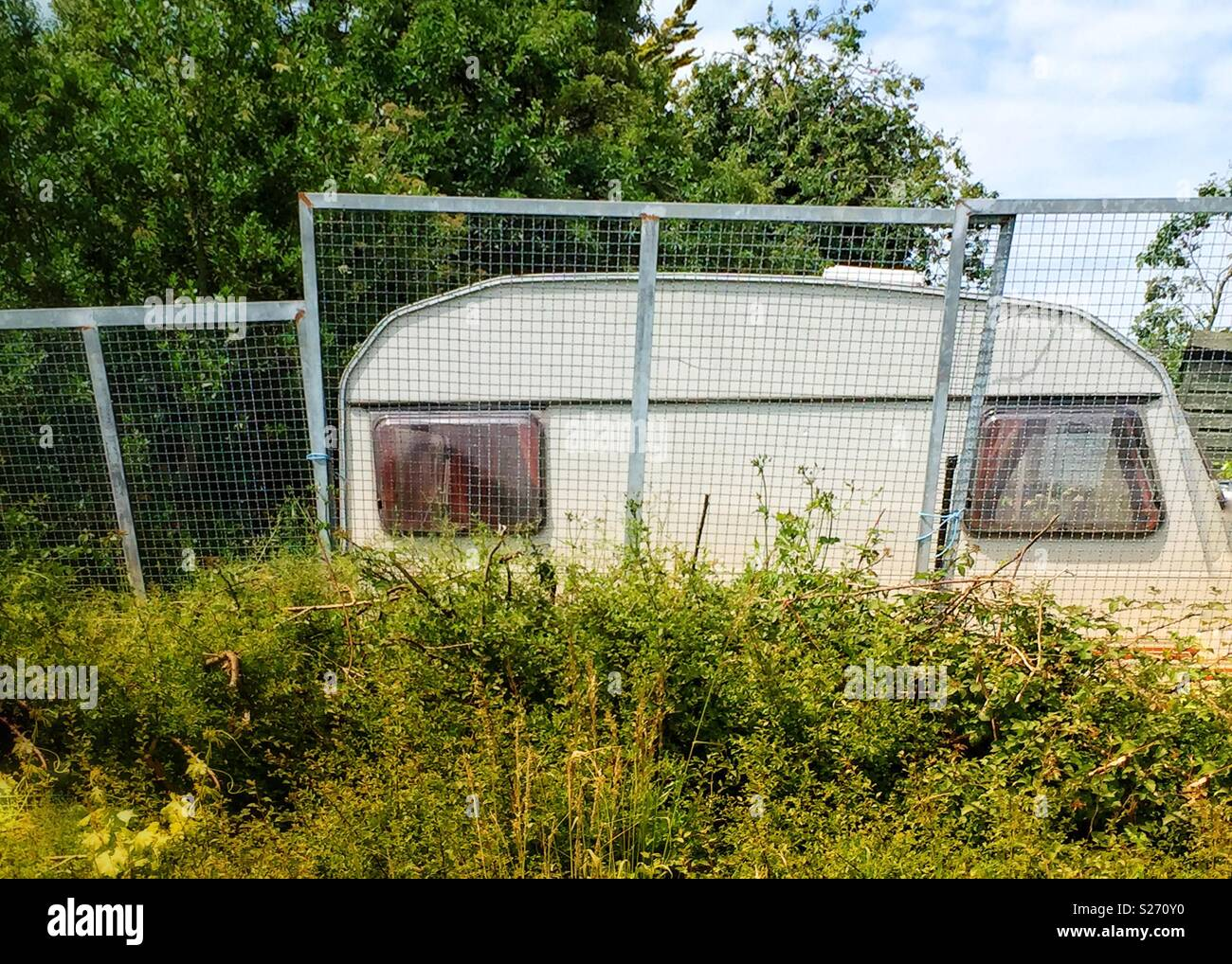 Caravan dumped in field - Stock Image