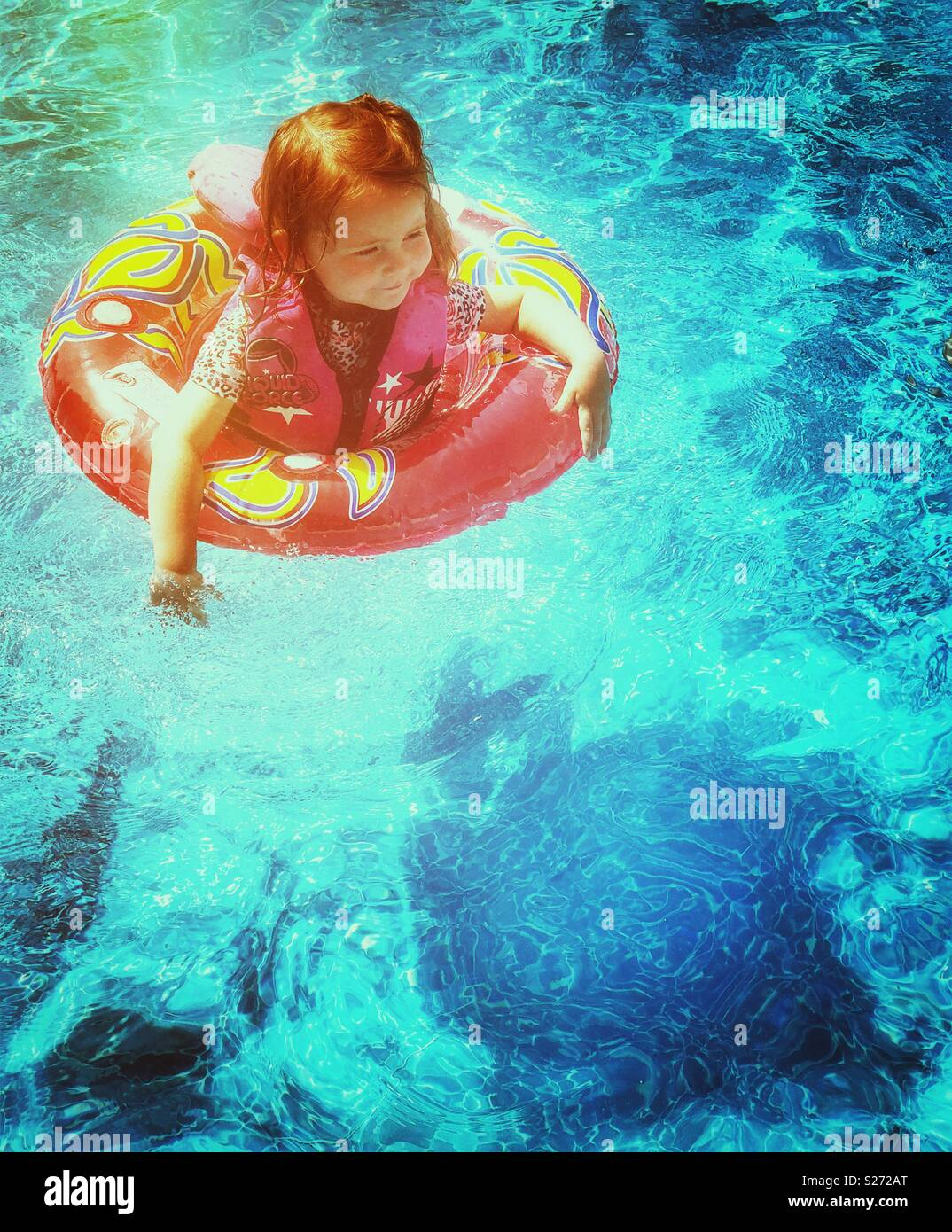 Toddler girl in a swimming pool with life vest and flotation ring on a summer day - Stock Image