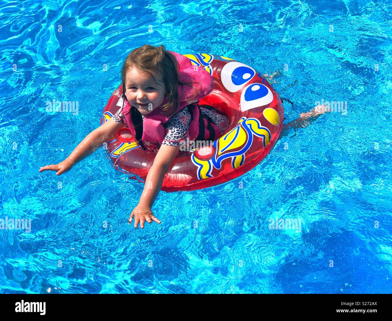 Toddler Girl In A Swimming Pool Wearing Life Vest And