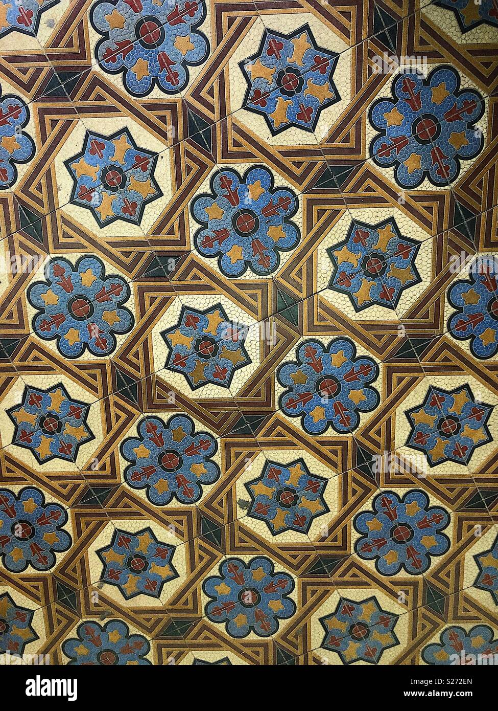 Tiled floor with decorative pattern of blues and creams - Stock Image