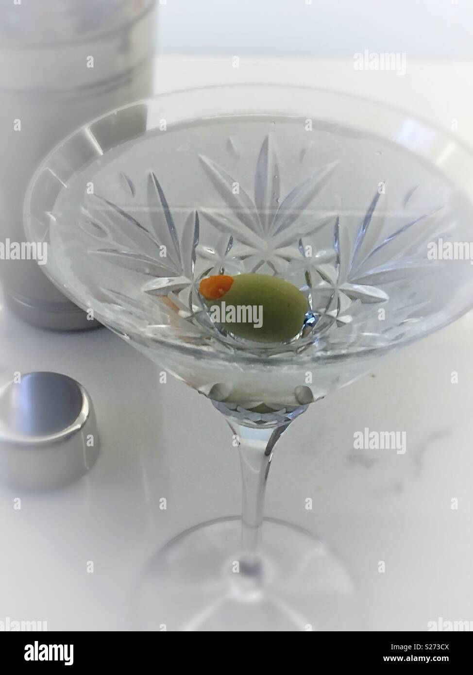 The classic dry gin martini next to a Cocktail shaker, served in a Waterford crystal martini glass, USA - Stock Image