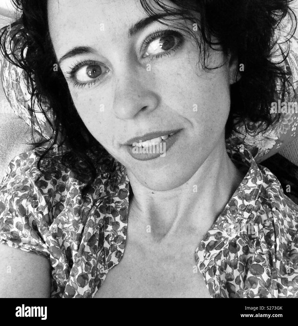 Black and white of women with dark wavy hair in her thirties looking sideways and smiling softly with a short sleeved floral top on - Stock Image