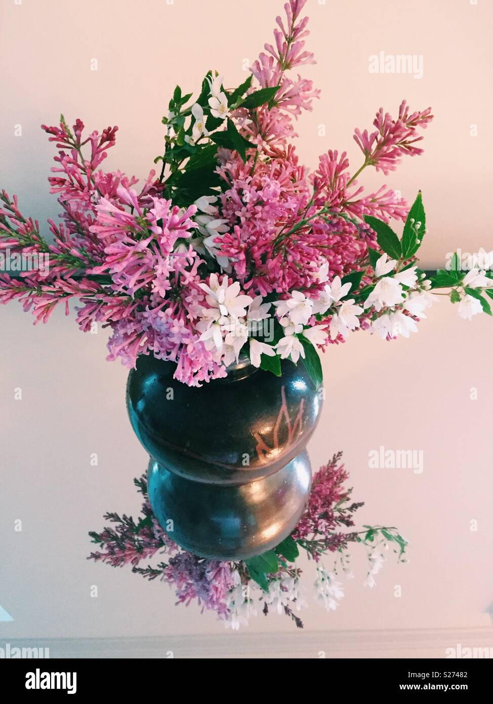 Spring flowers in pottery vase. - Stock Image