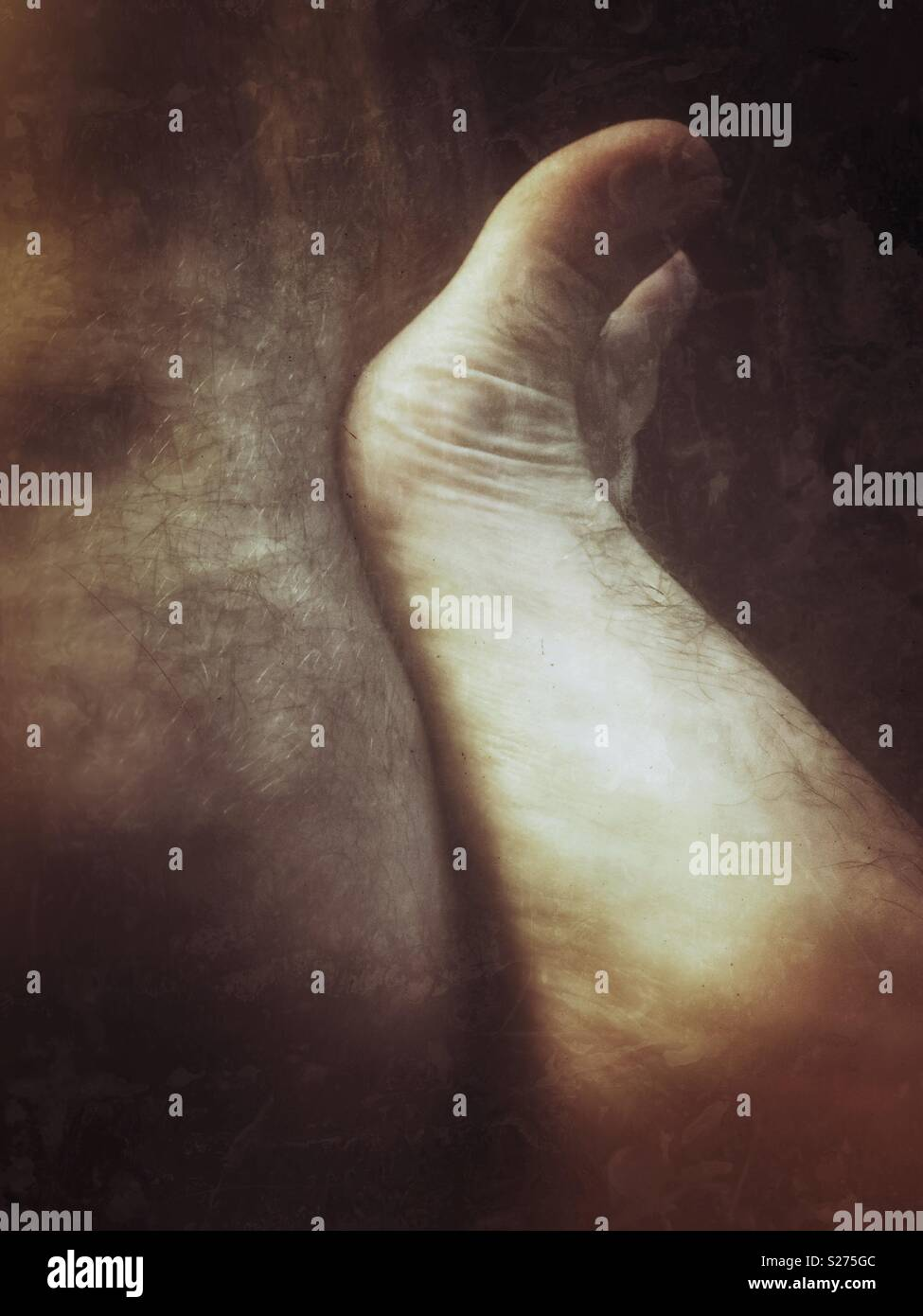 Foot against leg - Stock Image