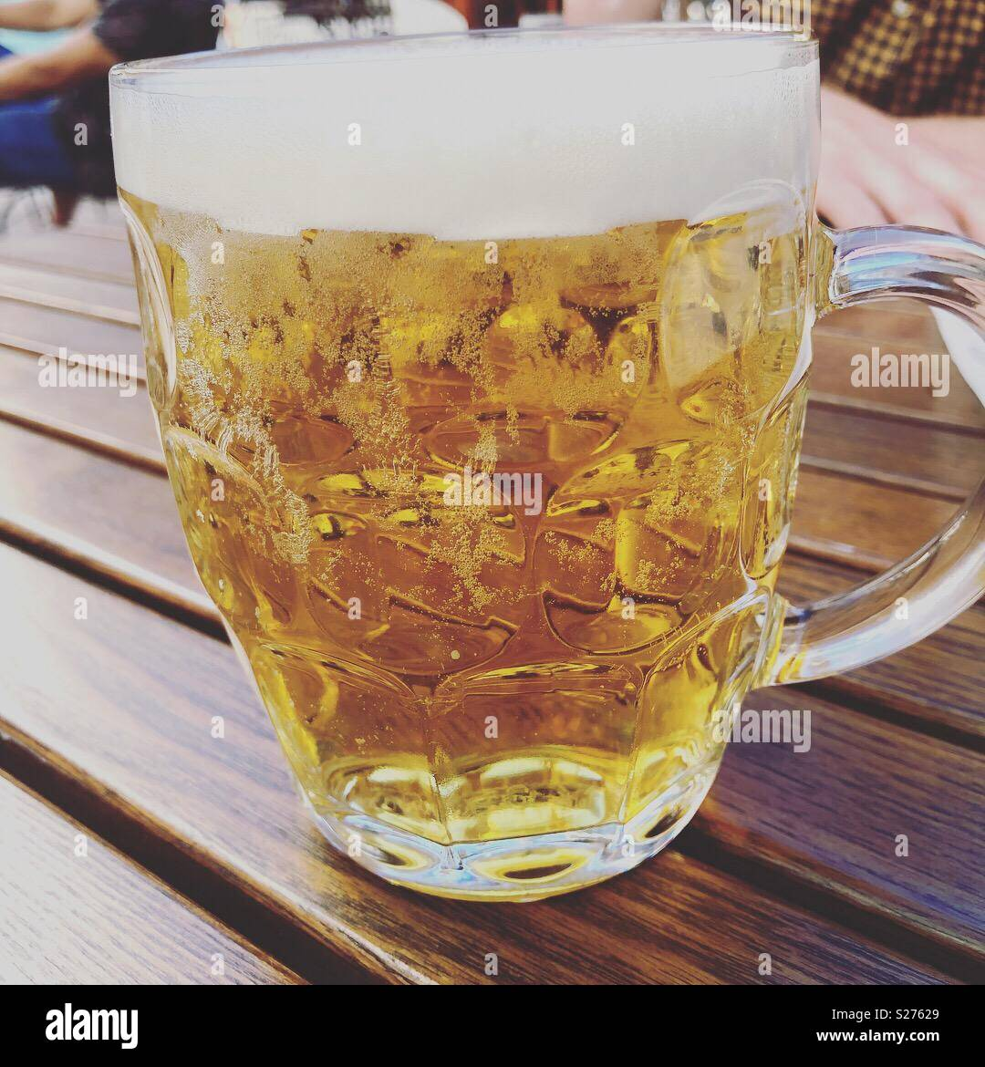 Old fashioned pint of beer on a wooden table outside a pub in springtime - Stock Image