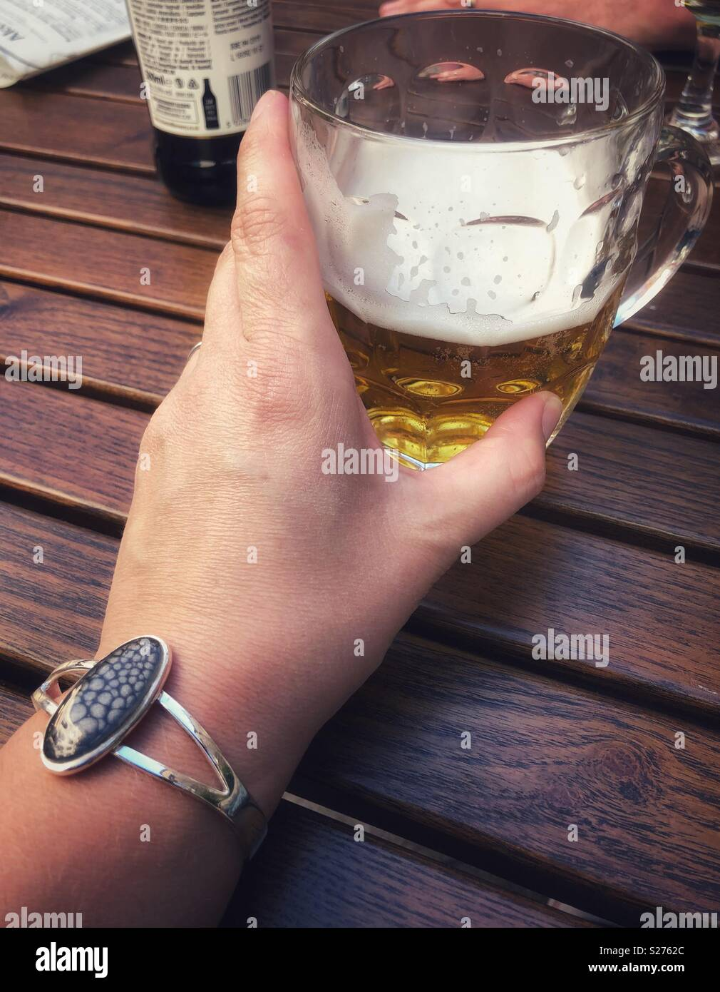 Woman holding a half drunk pint of beer in an old fashioned pint pot whilst sat by a wooden table. - Stock Image