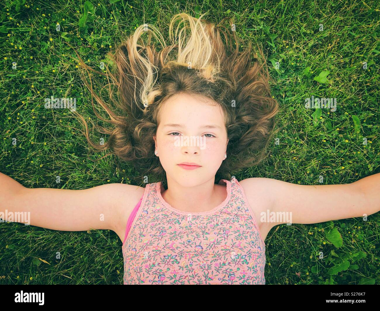 11 year old girl laying in the grass with arms out and serious expression on her face - Stock Image