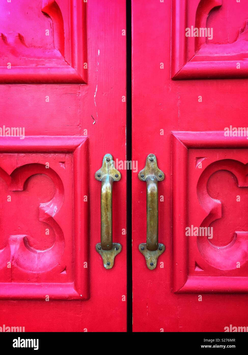Closeup of red doors with brass handles - Stock Image